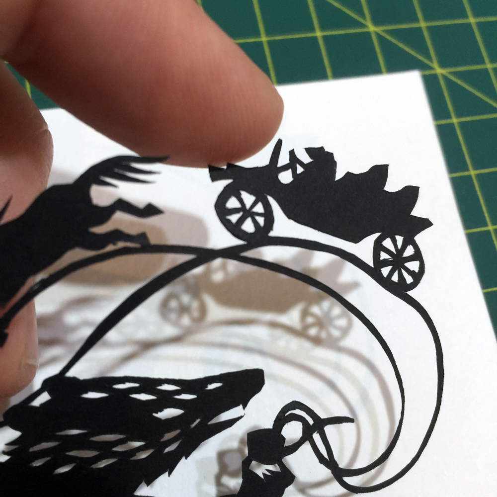 Detail of cut paper silhouette of Badger talking and smoking a pipe, with toad driving a car and a galloping horse on the smoke.
