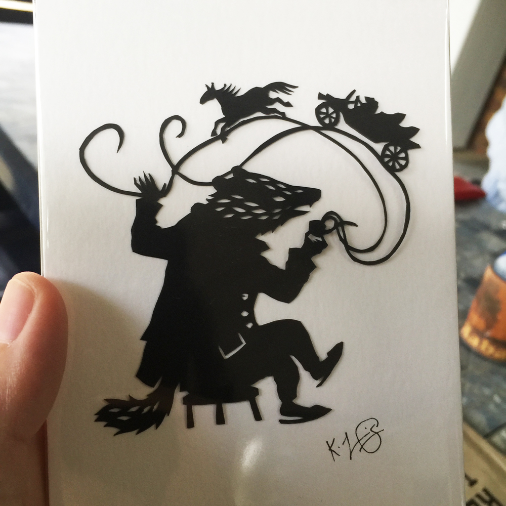 Cut paper silhouette of Badger talking and smoking a pipe, with toad driving a car and a galloping horse on the smoke.