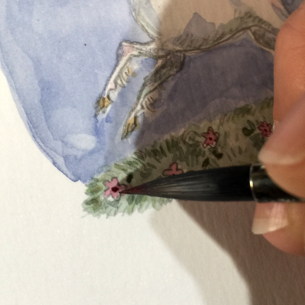 Detail of fingers and paintbrush painting flowers and unicorn.