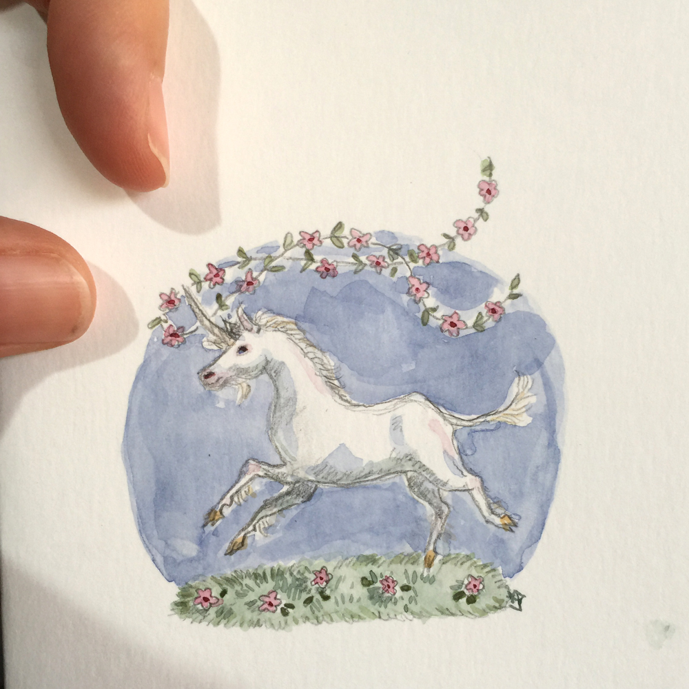 Pencil and watercolour drawing of a unicorn on a field of flowers, with a garland of flowers trailing from its horn.