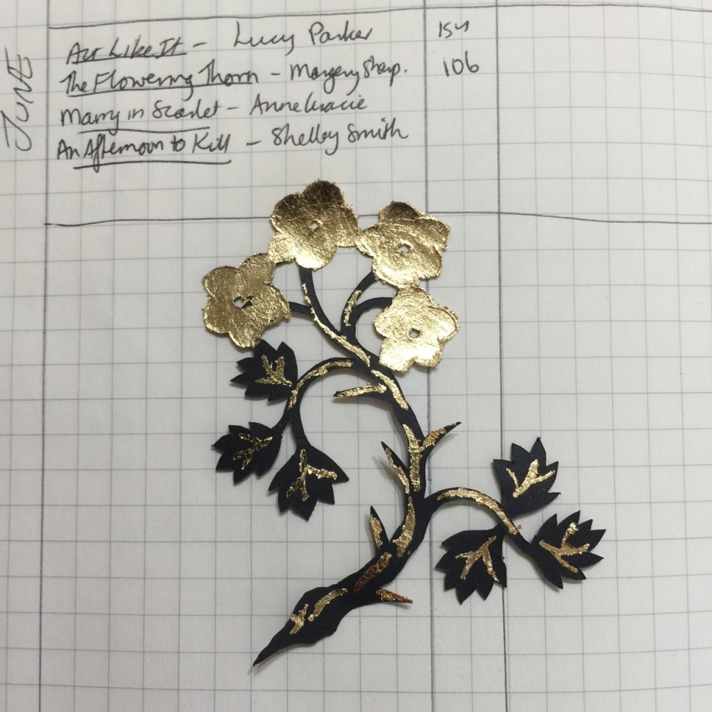 A cut-paper silhouette of a flowering thorn sprig with gold-leaf details, on the page of an open notebook with a hand-written book list