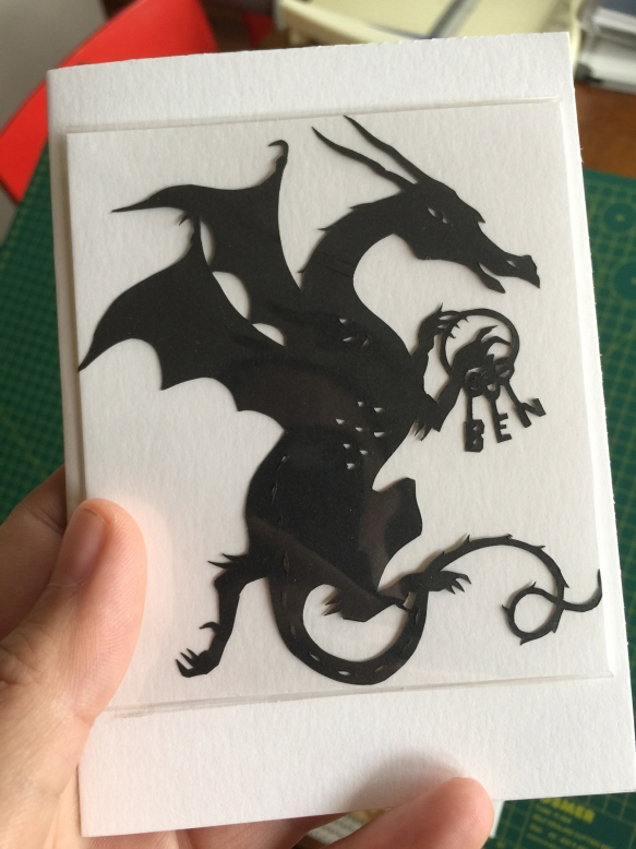"White card with a black cut-paper silhouette of a dragon holding a ring of keys that spell ""BEN"""