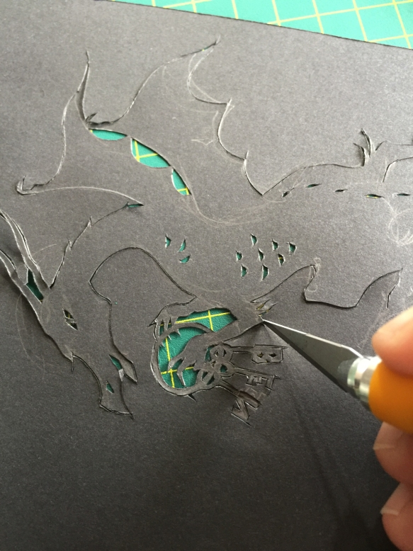 Fingertips and point of knife cutting out dragon.