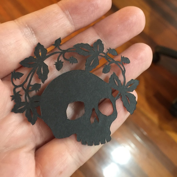 Hand holding cut-paper skull, in black paper, crowned by strawberries